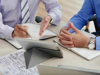 Close-up image of coworkers discussing data on tablet computer screen
